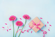 Spring composition with pink flowers and gift box on blue table top view. Greeting card for Birthday, Woman or Mothers Day. Flat lay.