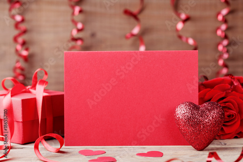 Foto Murales Valentines day mockup. Red heart, paper card and gift on wooden table.