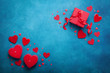Holiday background with gift box and red hearts on blue table top view. Valentines day card. Flat lay.