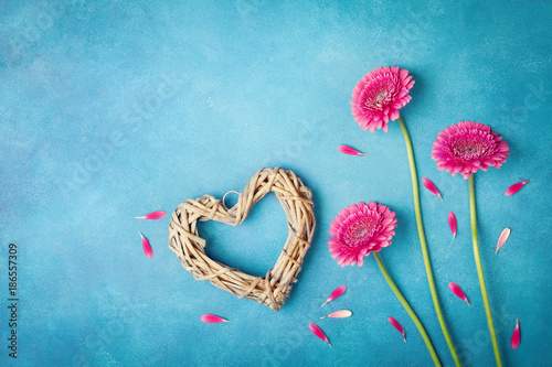 Greeting card for Woman or Mother day. Spring background with pink flowers, heart and petals. Flat lay style. Top view. - 186557309