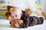 Fototapety Little baby boy playing at home with soft teddy bear toys