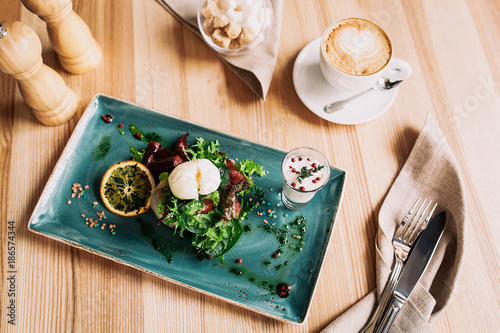 beautiful breakfast arrangement: Egg poached with sausages and lettuce leaves with a cup of coffee cappuccino on a wooden table - 186574344