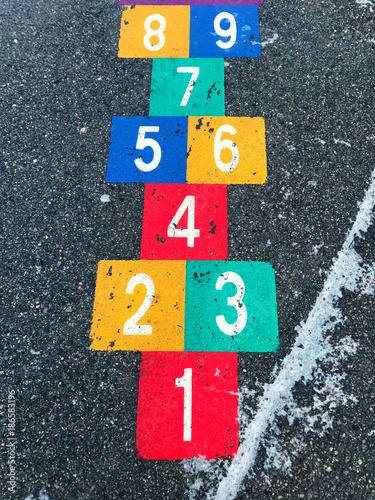 Foto Murales Hopscotch game painted on asphalt. Cold winter time. Asphalt frozen and slippery.