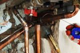 A worker is  soldering copper pipes. - 186595154