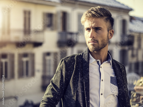 Foto Murales Handsome trendy blond man standing outdoor in European city setting with elegant old historic building behind