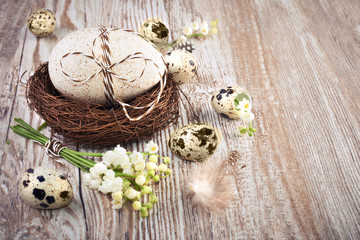 Bird's nest, eggs and lily of the valley on wood