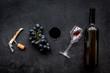 Open the wine. Corkscrew near bottle on black background top view