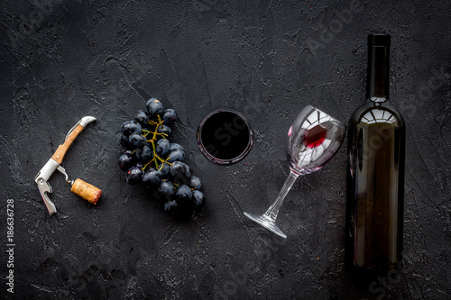 Open the wine. Corkscrew near bottle on black background top view - 186636728