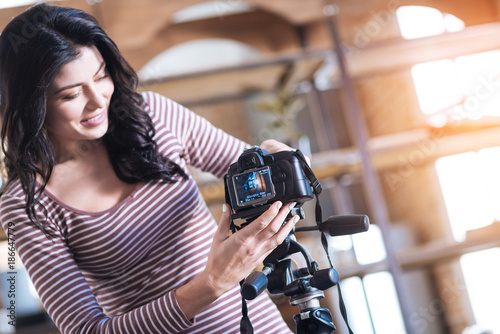 Preparation for video shooting. Cheerful nice young woman looking at the camera screen and smiling while preparing to shoot a video