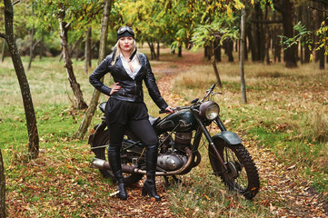 Young attractive girl with old bike in the autumn Park .Girl in retro clothes with retro motorcycle