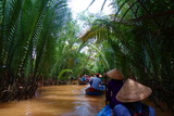 My Tho, Vietnam: Tourist at Mekong River Delta jungle cruise with unidentified craftman and fisherman rowing boats on flooding muddy lotus field in Mekong delta into Ho Chi minh city - 186668177