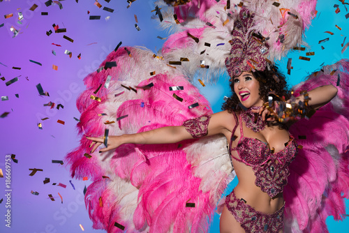 Foto Murales Happy young woman in carnival costume with pink feathers dancing and celebrating on blue background