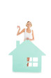 young woman with keys in hand standing near house model isolated on white