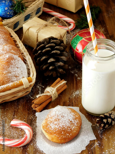 Foto op Aluminium Milkshake Donut berliner and a glass of milk surrounded by Christmas attributes on a wooden background