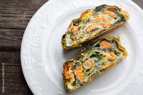 Strudel pie with salmon and spinach, served on wood table