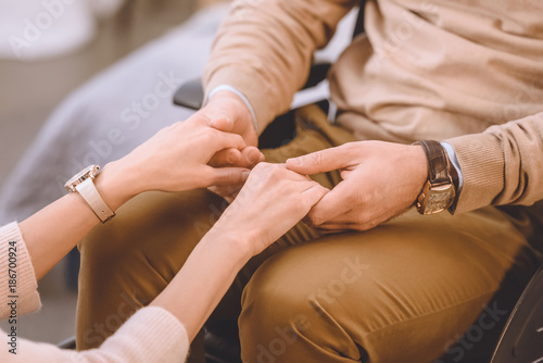 cropped image of husband on wheelchair and wife holding hands