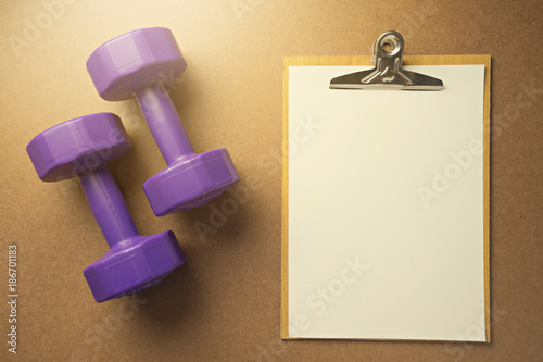 Flat lay design For healthy sport with blank paper on notepad and 2 purple dumbbell on wooden background.