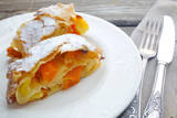 Strudel pumpkin and apple with raisins on parchment, fruit and vegetables on a dark wooden board