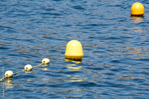 Foto Murales Line of yellow buoys against the blue sea. Restriction on open water. Glare and ripples on the water