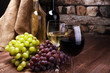 Quadro Red Wine bottle and white wine with grapes and glasses on wooden background
