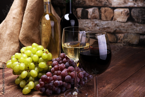 Foto Murales Red Wine bottle and white wine with grapes and glasses on wooden background