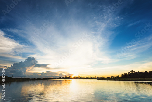 Keuken foto achterwand Beige Sunset landscape with blue sky and fluffy clouds over lake