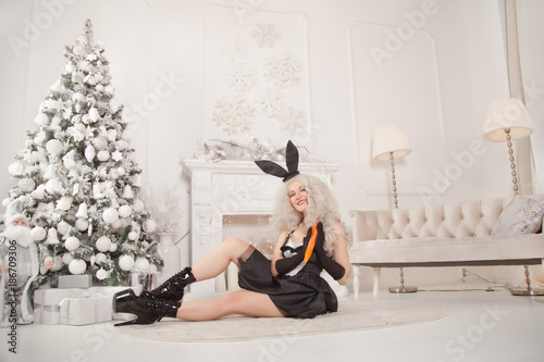 beautiful slim girl in black sexy rabbit dress posing with a carrot near the christmas tree and white fireplace with new year gifts - 186709306