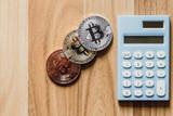bitcoin digital cryptocurrency with calculator on wood floor - 186723967