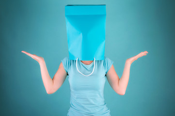 Woman with shopping bag over her head. Shopping metaphor.