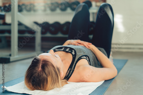 Wall mural Young woman working out on a mat in a gym