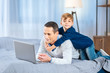 Gentle hug. Adorable little boy back-hugging his beloved father lying on the bed and working on the laptop