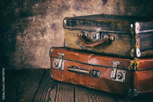 Foto Murales Fragment of old leather suitcases on wooden table