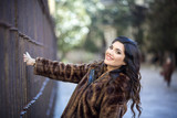 young and beautiful smiling brunette woman with fur coat grabbed to iron grate