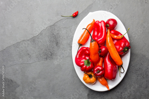 Chili and bell pepper on white plate, slate background, top view - 186745369