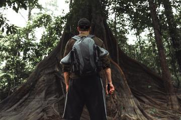 Mann steht vor einem alten baum im Dschungel von Kolumbien am Amazonas