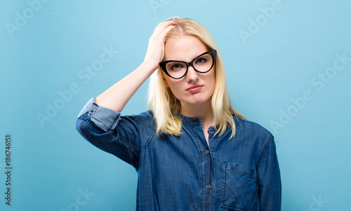Young woman feeling stressed on a solid background - 186746151