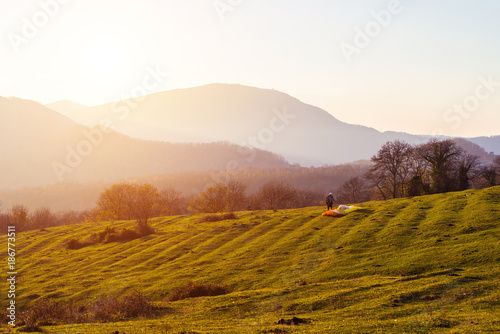 Fotobehang Wit Sunset landscape field and mountains, paraglider exercises to fly