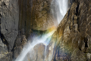 Waterfall Curves Through Granite Cliff with Rainbow