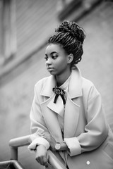 Stylish African girl in the blue coat in the style fashion stands and leans on the railing outdoor black and white image