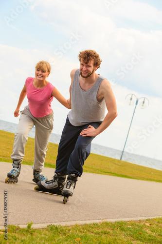 Man encourage woman to do rollerblading