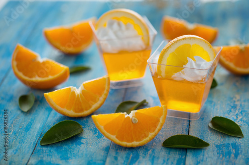 Orange jelly in a cup with whipped cream and orange sliced on blue wooden background