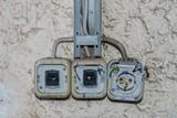 Kaputte Lichtschalter und Steckdose an einer Hausmauer - 186841587