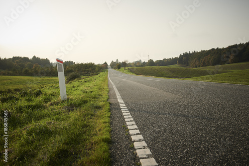 Fotobehang Wit Landscape with green fields and a long road disappearing out in the horizon.