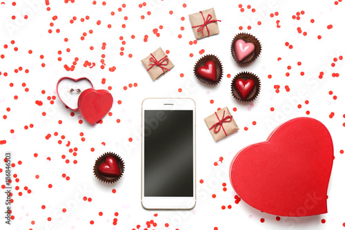 Minimal styled Valentine's Day flat lay top view isolated on white background. Mobile phone with empty screen, gifts, heart-shaped candies, engagement ring, pink and red confetti. Love concept