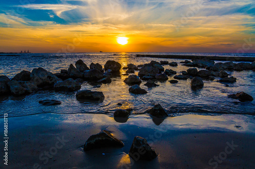 Keuken foto achterwand Zee zonsondergang Large stones on a sandy beach