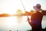 Young man fishing on a lake at sunset and enjoying hobby - 186854358