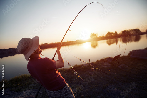 Men fishing in sunset and relaxing while enjoying hobby