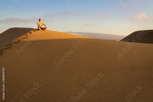 Man sitting and relaxing on sand dunes by the sunrise, in Maspalomas on Gran Canaria. - 186864784