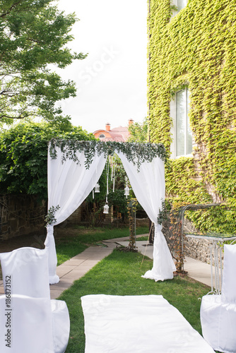 Foto Murales Beautiful square wedding arch, decorated with white cloth and greenery, standing in the garden for newlyweds and their guests