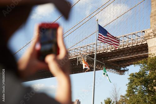 Fotobehang Brooklyn Bridge Tourist Taking Photo Of Brooklyn Bridge On Mobile Phone